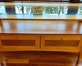 "Lot 1540  $120.00  Matching Sofa Table with Beveled Glass Top and Middle Shelf, Finished in Maple and Cherry Veneers, The Top Surface shows wear and rough spots by Riverside Furniture 48"" L x 16"" D x 28"" H"