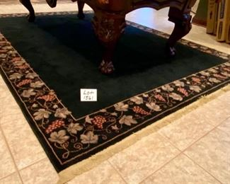 "Lot 1561 $325.00. Nice Black Rug with Tan Leaf and Grape Leaf Design around the rim and Tan Fringe 134"" L x 91"" W (10'10"" x 7'7"")"