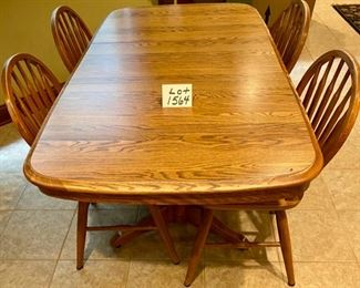 "Lot 1564  $275.00  Solid  Oak Kitchen Table w/ Under Table Leaf Storage and 4 Oak Spindle Back Chairs.  Great for a Growing Family. Includes 1 Leaf.  49.5"" L w/o Leaf x 34"" W,  Leaf is 17.75"" W.  Shown with Leaf"