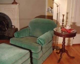 Living Room:  A pretty green occasional chair and matching ottoman with braid cording is to the left of a small one-drawer vintage drum table.  Also shown is a heavy vintage brass floor lamp and other decorative items.