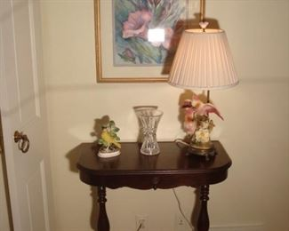 Living Room:  A vintage one-drawer table displays a bird figure and vintage porcelain bird lamp.  A crystal vase is also shown under the floral print.