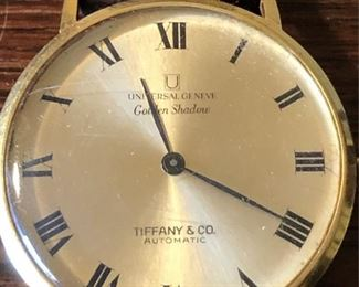 18K Gold Tiffany & Co Universal Geneve Golden Shadow Watch 25 Jewels. Marked 18k on inside of case. Original Tiffany & co leather wristband marked 18k on clasp.  25 Jewels 2 Adjustments Automatic Swiss movement