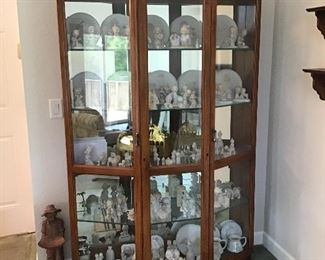 Huge lighted curio display cabinet full of a collection of Precious Moments Figurines.