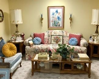 Lower level family room, marble top tables, blue velvet chair , floral sofa, retro lamps