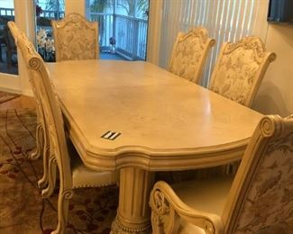 "Dining Room table (85"" L x 45"" W x 30"" H). Includes 2 additional leaves measuring 24"" W each. Table includes 8 chairs (2 of which are captains chairs). Color is light almond beige with silver, brown & gold inlays to give an elegant look and feel. Original cost $8,000 (ASKING $2,300)"