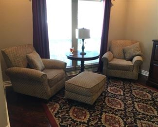 Upholstered chairs with ottoman, area rug and round side table