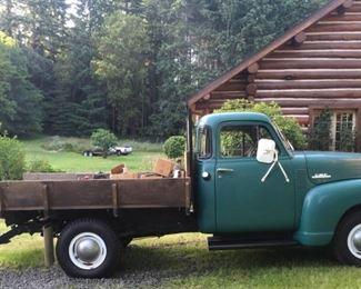 1951 GMC truck in yard of log home