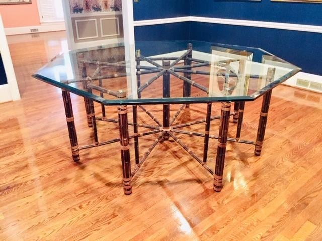 McGuire, Baker--Large octagonal bamboo rattan dining table made in the California organic modern style McGuire for Baker. Features an iron frame 62 inches wide completely wrapped with bamboo poles. The bamboo is lashed together with leather rawhide laces. The table has 9 legs making a beautiful geometric star shaped form. Topped with a pane of 3/4 inch thick beveled glass in an octagonal design. Each leg has a height adjustable foot on the bottom. Excellent joinery and craftsmanship.