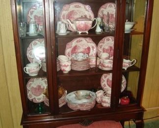 Antique walnut china cabinet with glass door and sides filled with Mason's Castle china