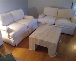 Pair of ivory loveseats. Marble cocktail table