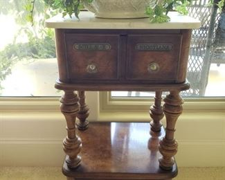 """https://ctbids.com/#!/description/share/545543 Very unique piece that will add character to your home. *Reserve Price Set For $250* Apothecary side table with marble top and casters. Greenery is included. 14.5"""" deep. See photos for other measurements. """"These tables were very popular in the late 1800's and early 1900's when home remedies (homeopathy) was popular. Nicotiana were drugs from various nicotine plants. Scill AE R were drugs derived from scillae plants."""""""