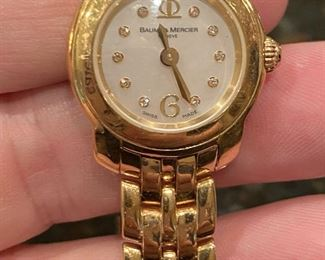 Baum & Mercier Ladies 18k gold watch, with mother of pearl and diamond face. In excellent working condition.