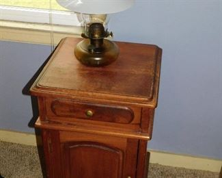Small antique table, oil lamp with milk glass shade.