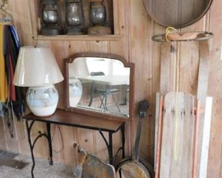 Old toboggan, railroad lanterns, wood and iron narrow table on casters, antique sieve, dead banjo.
