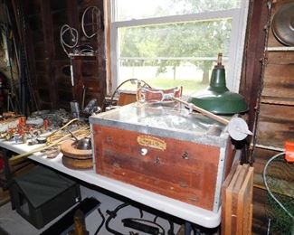 Table full of metal artist objects and an antique chick incubator