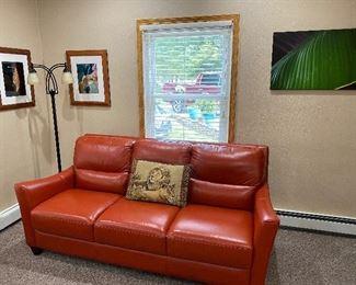 Leather sofa, Framed Keating photos, Floor lamp