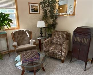 Chair to left is swivel rocker.  Patterned upholstery chair is a recliner. Glass top tables, Live plants, and the Phonograph from about 1920.