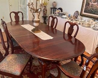 Mahogany table with 2 extension  leaves & six chairs (2 are arm chairs)