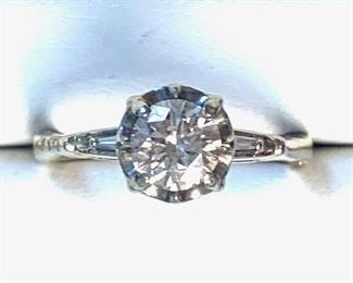 This is a 14KT white gold cast diamond engagement ring with an illusion set round brilliant cut diamond with an approximate weight of 0.80ct. You will also see there are two prong set baguette cut diamonds with an approximate total weight of 0.10ct.