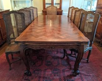 "Amazingly large French walnut dining table, with extendable leaves on both ends, set of 12 chairs (pair of arms, 10 sides), matching buffet and bonnetiere.            The French table measures 8' 6""L x 3' 8"" W x  2' 6""T, with 27"" extensions on each end."
