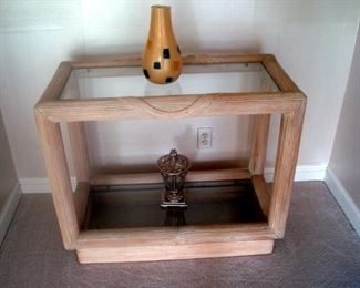 Reeded wood side table with glass shelves.