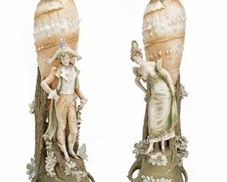 """8 An Opposing Pair Of RStK Amphora Shell Vases Circa 1892-1905; Teplitz, Austria Each marked for Riessner, Stellmacher & Kessel Turn-Teplitz; Further stamped: 1138 / 8 The opposing male and female figures each with a large shell and floral base, 2 pieces Each approximately: 26.5"""" H x 8"""" W x 11"""" D Estimate: $1,500 - $2,500"""