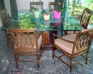 One of two glass top pedestal tales with sets of chairs.