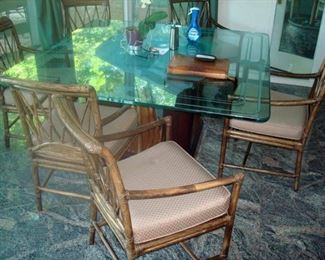 One of two glass top pedestal tables with set of chairs.
