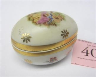 """A 1.75"""" wide porcelain trinket box in the form of an egg. Marked limoge France. Transfer image of a couple on the lid"""
