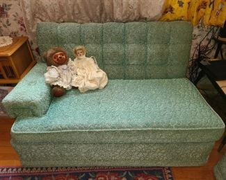 One part of a teal couch with wheels