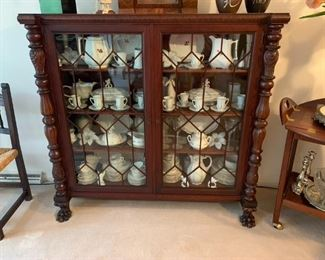 Antique American Empire bookcase with claw feet & carved columns.