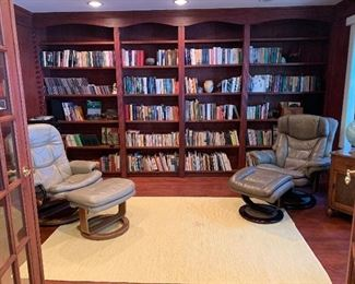 Library filled with books and Leather Recliners