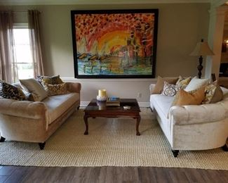 The two Z Gallerie sofas, a cherry coffee table, and a large oil painting
