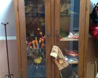 Handmade gun cabinet filled with fall decor (including tablecloth, florals etc.  Also to the left one of the iron candleholders
