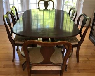 Antique mahogany empire double pedestal dining table with 6 chairs.  Includes two additional leaves not in photo.