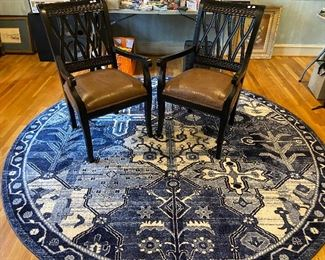 8 ft round rug in blue and white.  Pair of wooden arm chairs with leather cushion seats.
