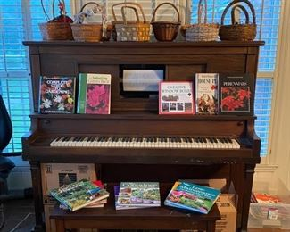 Player Piano with several boxes of music rolls