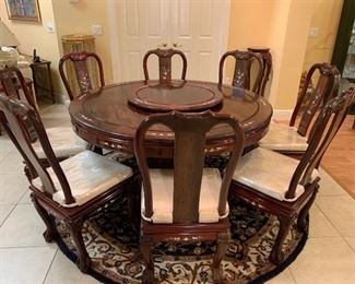 """Oriental teakwood dining table and 8 side chairs. 20/21 C. Custom made with Mother-of-pearl inlay and center Lazy-Susan. In the """"Ming"""" style, the chairs with pad cushion seats. $1500"""