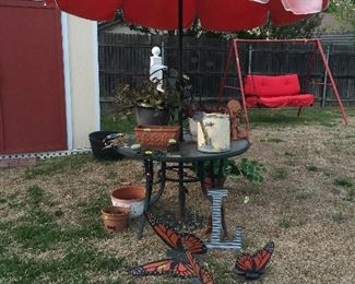 Garden table with umbrella, plants, and lots of decorations