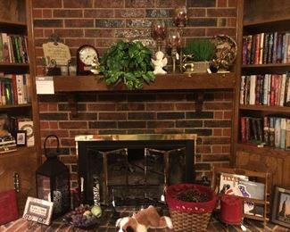 The fireplace has Christmas stocking holders, floral, glass candle sticks, art, candle holders