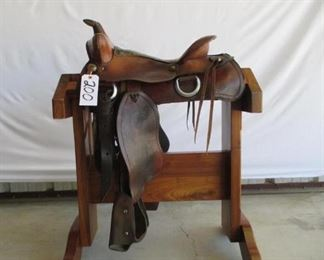 200	  Cowboy Ranch Saddle Western Ranch Saddle.  15 1/2 inch seat.  Kids size safety tapadero stirrups.  Saddle complete with latigo, cinch and string ties.  Saddle has vintage string conchos.  Saddle is in using condition.