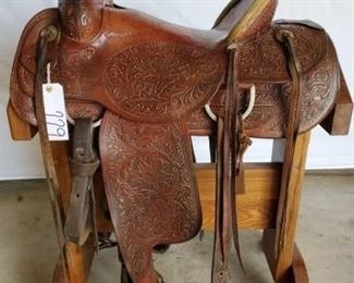"229	  Custom Santa Fe Roping Saddle 16 1/2"" Santa Fe Roping Saddle.  Deep leather carving.  4 1/2"" rawhide pencil roll cantle. Vintage conchos.  Front and back cinches.  Makers mark.  In good working condition"