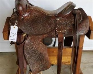 "244	  Cowboy Roping Saddle 16"" western roping saddle.  Has a complete rigging.  The breast collar is a Billy Cook.  Nice buck stitching in the seat. Saddle is in working condition. Small tear on left side fender, see photos."