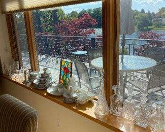 Full window sill of crystal vases & decanters.