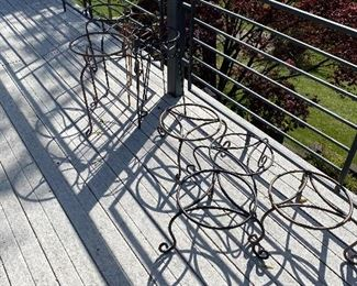Many wrought iron plant stands.