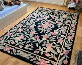 Large floral hooked area rug.