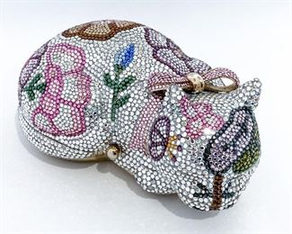 """Judith Leiber white cat clutch with multi-color crystal flowers. Bottom is lined with gold leather. Opens from the side to reveal an open cavity at the base and a pocket to secure items in the top. Comes with double-sided mirror, tasseled comb, and coin purse. Size is 6.125"""" length, 4"""" height, and 3.875"""" depth. Condition is excellent with very few crystals missing. $1895"""