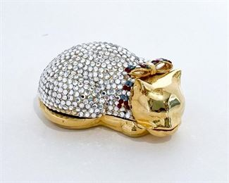"""Judith Leiber cat pill box. Gold body with white/silver crystals, deep red and blue crystals on the bow. Opens to reveal a hollow, gold cavity. """"Judith Leiber"""" signed on the tail tab. Size is 2.5"""" length, 1"""" height, and 1.5"""" depth. $325"""