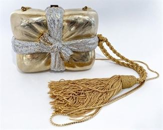 """Judith Leiber gold rectangle present with a large tassel. Opens to a gold leather lined interior. Comes with double-sided mirror, tasseled comb, and coin purse. Marked """"Judith Leiber New York"""" inside. Size is 6.5"""" length, 4.625"""" height, and 2.5"""" depth. Braided gold metal strap is 40"""" long. Condition is very good with some crystals missing. $895"""
