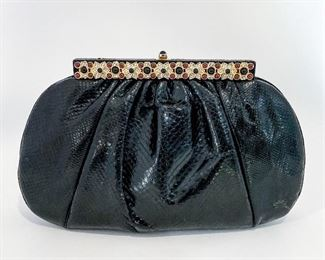 """Judith Leiber black snakeskin bag with red, black, and white stone/crystal closure embellishment. Both sides of the bag feature the decorative geometric trim. Opens to black silky lining with a zipper and an open pocket. Comes with double-sided mirror, tasseled comb, and coin purse. Size is 10.25"""" length, 6.25"""" height, and 3.125"""" depth. Thin leather strap is 39.5"""" long. Can be used as a clutch or crossbody. Condition is excellent. $495"""